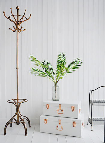 Artificial Green pal with copper coat stand and Nantucket trunks from The White Lighthouse Furniture