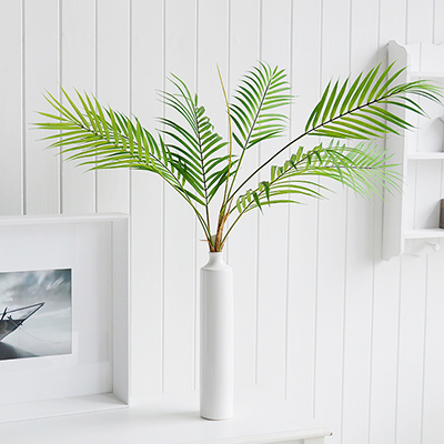 A Green Artificial Fine Palm bush in a tall white ceramic vase