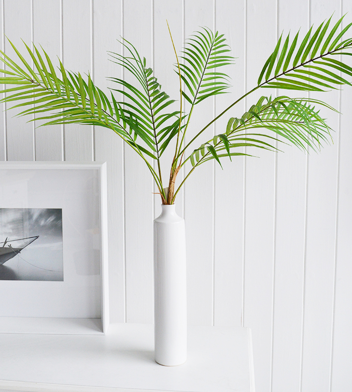A fabulously realistic green palm stalk with seven fine palm fronds, each detailed leaf structure is variated with a lighter green nearer the stalks to resemble new growth.  The tall simple white ceramic vase is included