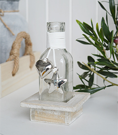 A decorative square bottle with a hanging silver mirrored chunky heart and star in a driftwood style wooden crate for New England coastal and country interiors and white furniture
