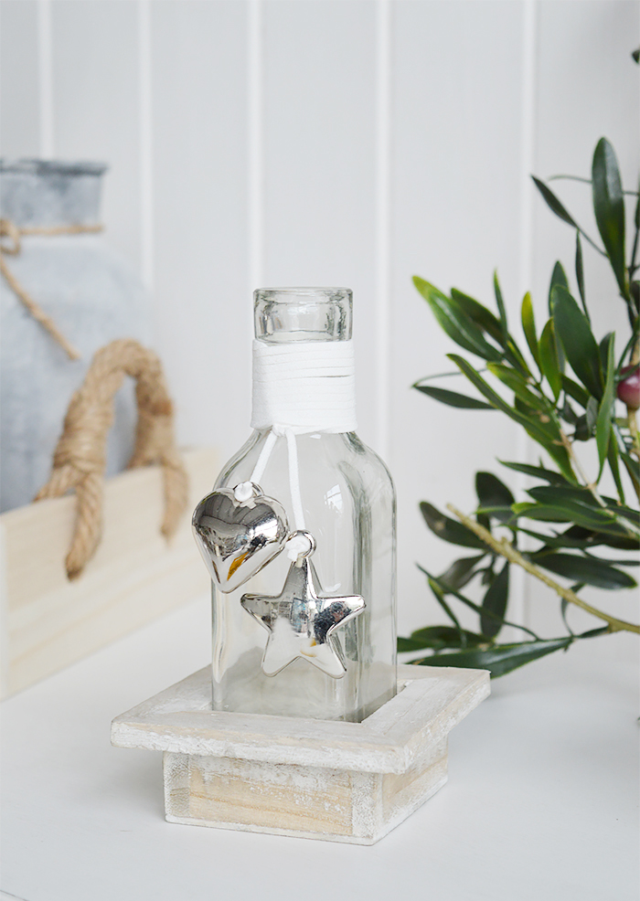 A decorative square bottle with a hanging silver mirrored chunky heart and star in a driftwood style wooden crate