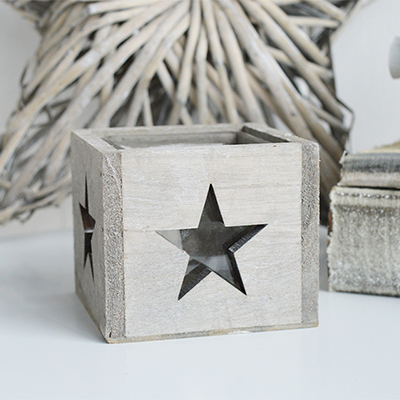 The Nantucket wooden candle holder with glass cup for a candle and a cut out star on all four sides for the candlelight to light up the stars