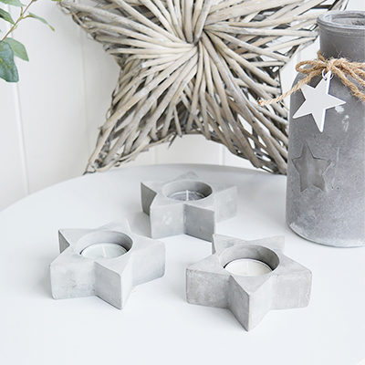 A set of 3 star tea light holders in grey stone.