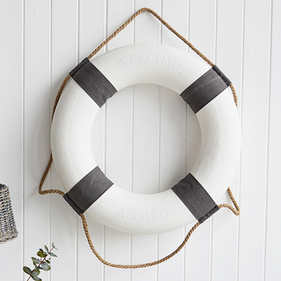 A white and grey vintage style lifebuoy.The complementing grey and white along with the natural rope and subtle Welcome Aboard offer a touch of Coastal Chic decor to your room.