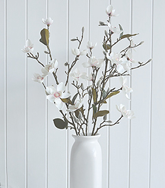 An artificial Magnolia branch with multiple flowers, leaves and buds on a realistic stem