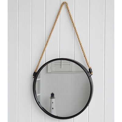 A circular porthole style mirror on a rope with aged dark grey metal surround.