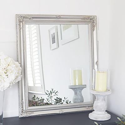 A silver wall mirror with decorative carved Fleur De Lis detailed chunky silver frame for a chic style to any bedroom, living room, hall or bathroom. The mirror can be wall hung or simply rest on a table top for dressing or console table.
