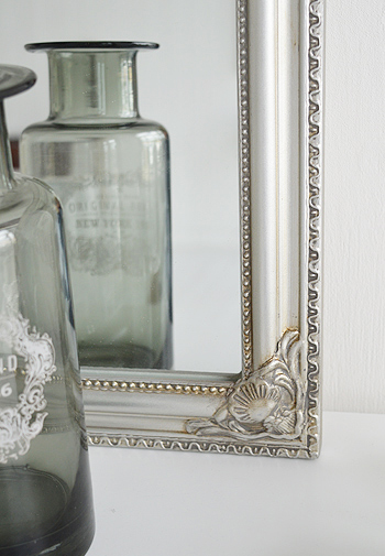 Close photograph of ornate silver mirror on the dressing table