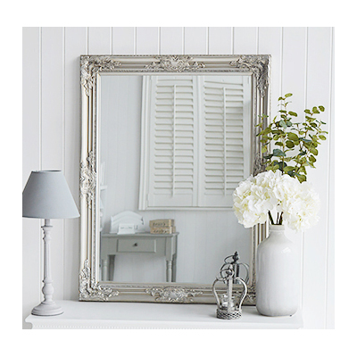 A large silver wall mirror with decorative carved Fleur De Lis detailed chunky silver frame for a chic style to any bedroom, living room, hall or bathroom. The mirror can be wall hung or simply rest on a table top for dressing or console table.