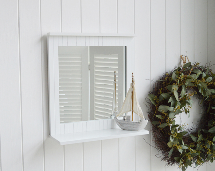 White bathroom mirror with a shelf for decorating a white bathroom in New England style