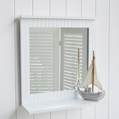 A white bathroom mirror with a shelf.