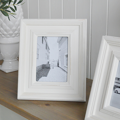 A chunky white wood photo frame for photos in a distressed white beach house finish.
