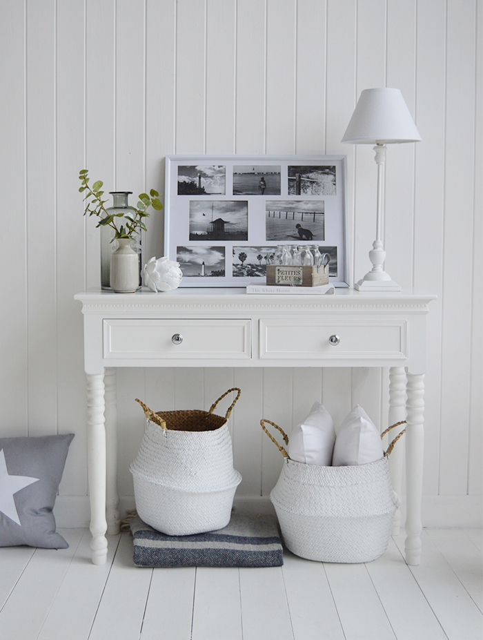 Style your New England white console table with photo frames, white lamps and home decor pieces, shown with baskets underneath for extra hall storage