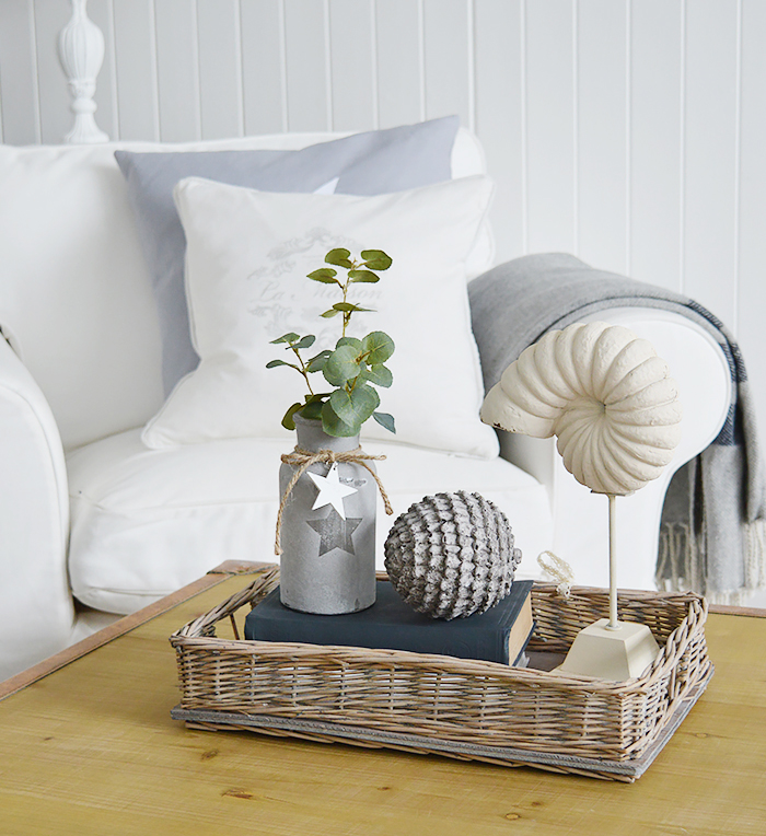 Coastal style home decor accessories. The Decorative shell on a stand in the willow tray
