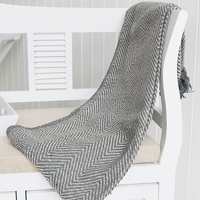 A grey woven herringbone throw, bedspread or blanket with fringed edges