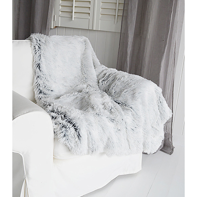 A cosy luxuriously soft silky grey throw with white suede effect back.