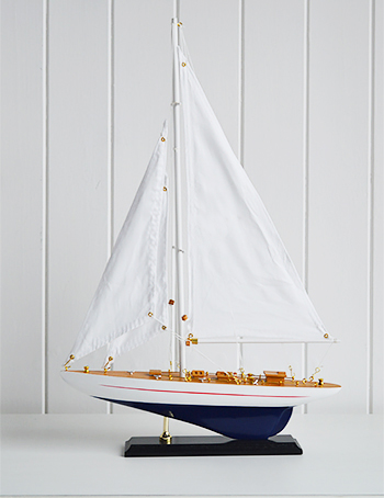 A wooden yacht in white and ble for hpomes by the sea
