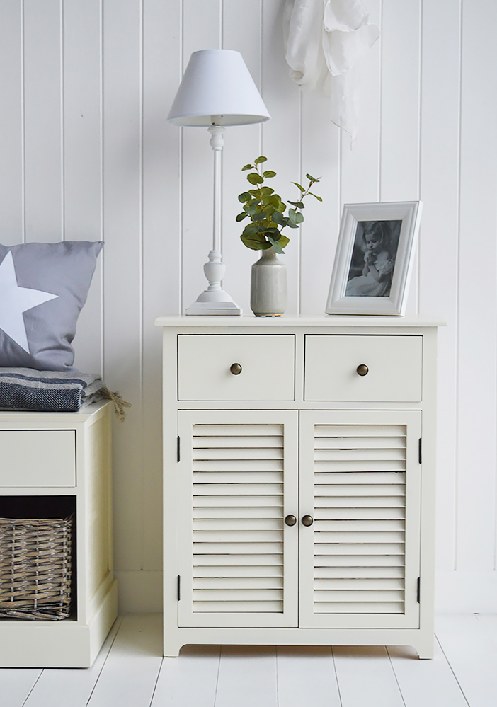 The Newbury cream cabinet with two top drawers with antique brass coloured knob handles and a large shelved cupboard with shutter style doors..The Newbury cream cabinet with its louvre style door, clean straight lines is a perfect match for every style of home interiors