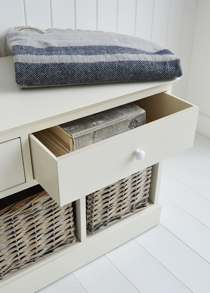 The large top drawer of the cream storage hall bench with books inside
