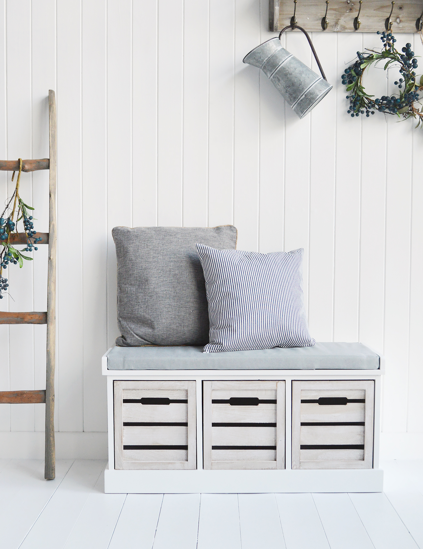 The Hartford Storage Bench with grey fabric cushion and three large crate drawers.  In a slightly distressed painted white finish the frame of the Hartford storage bench beautifully complements the washed wood colour of the three drawers  A gorgeous piece in the hallway, living room, bedroom or bathroom, designed to suit all New England style interiros for country, coastal, farmhouse and city homes