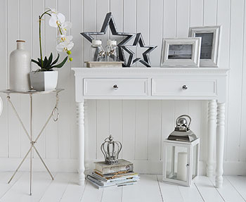 A white console table with two drawers and polished silver colour handles. The New England Range is a crisp white range of furniture for a sophisticated and classic look to any colour of hallway. The turned legs are in perfect proportion to the simple but elegantly designed table top. The drawers provide plenty of essential storage for your everyday items.