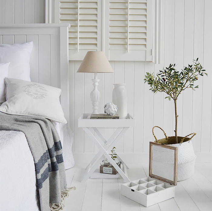 Classic New England style of furniture for the bedroom, adding texture warms the room, giving it a more cosy feel. A touch of greenery gives extra interest. The shutters and white cladding give the traditional look
