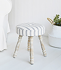 The Long Island small stool, padded and upholstered in ticking linen effect fabric with white washed turned legs for country and coastal home interiors.