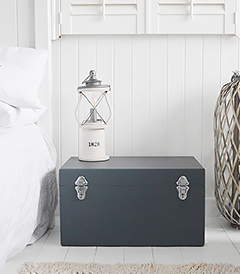 A set of two large different sized Newbury rectangle trunks in a luxurious dark blue grey colour in a matt finish with contrasting silver handles and clasps. The White Lighthouse New England Coastal and Country furniture and interiors. Bathroom, Living Room, Bedroom and Hallway Furniture for beautiful homes bedside table