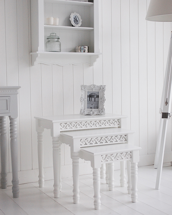 Image shows the white nest of three tables in a living room setting.