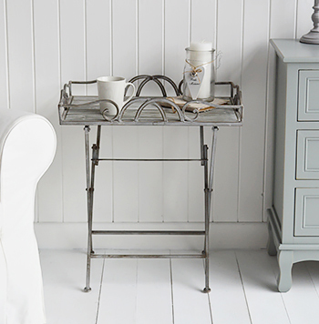 The Grayswood metal folding side table with a grey wood table top and elegant swirling edges. Finished in aged grey effect this is a wonderful and affordable option for small hallway furniture