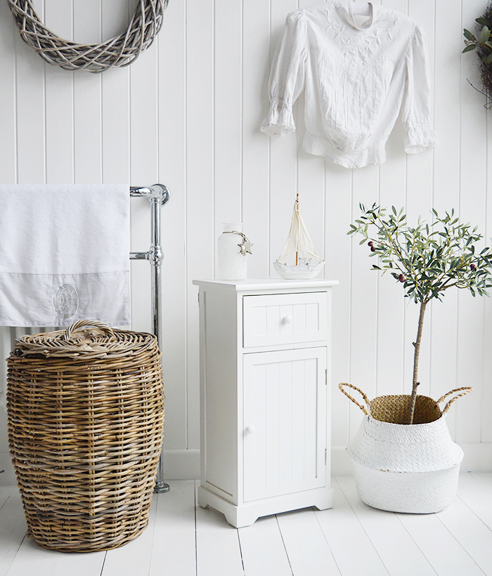 Maine white bathroom cabinet. White Furniture for storage with a cupboard and drawer. Photograph shows the cabine in a white bedroom beside the Casco Bay laundry basket