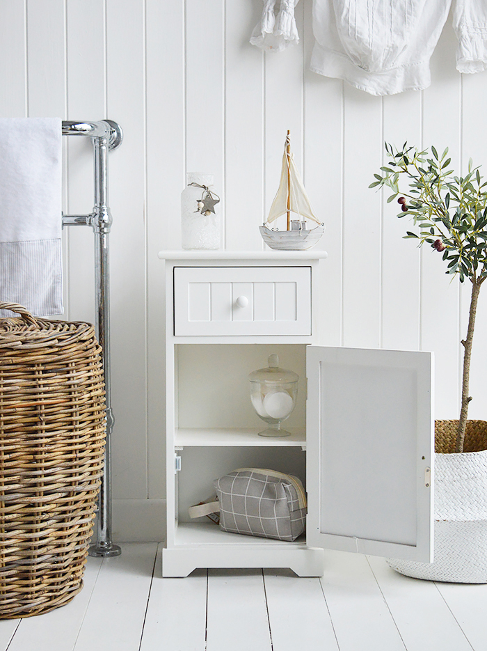 Maine white bathroom cabinet. White Furniture for storage with a cupboard and drawer. Photograph shows the cabinet open for storage