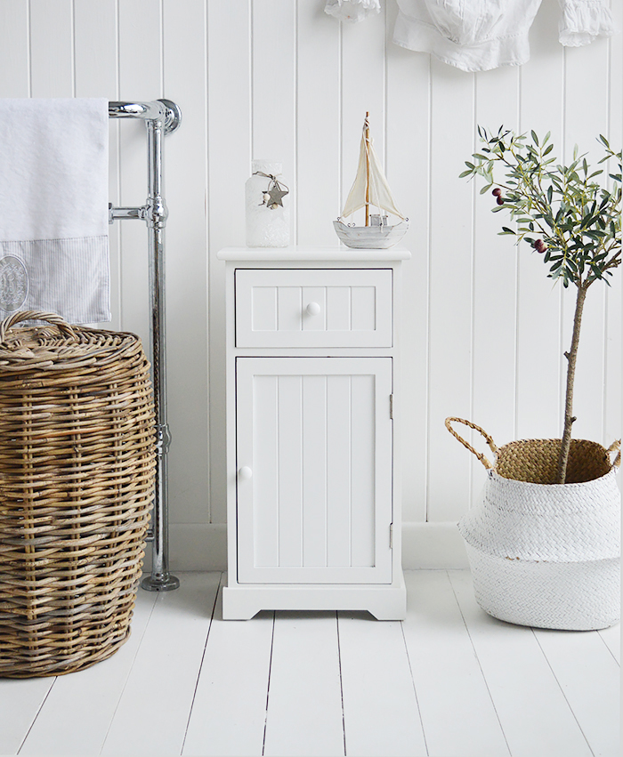 Maine white bathroom cabinet. White Furniture for storage with a cupboard and drawer. Bathroom decorating ideas for a coastal home