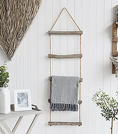 A rope ladder with driftwood effect rungs to hang towels, throws or blankets for a nautical coastal styled living room - blanket ladder from The White Lighthouse Furniture , New England interiors and furniture for the hallway, living room, bedroom and bathroom.