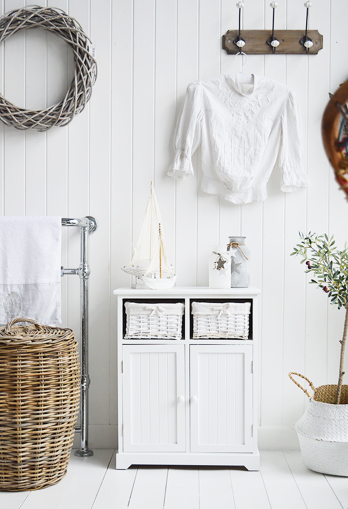 Maine white large bathroom cabinet. Furniture for storage in the bathroom for New England, country, coastal and city home interiors. Photogrpah for ideas in decorating a white bathroom
