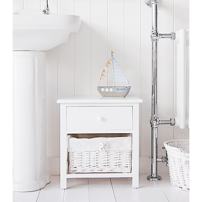 A painted white two drawer bathroom storage unit. The bottom drawer is a white lined willow basket, the top drawer has a simple knob pull handle