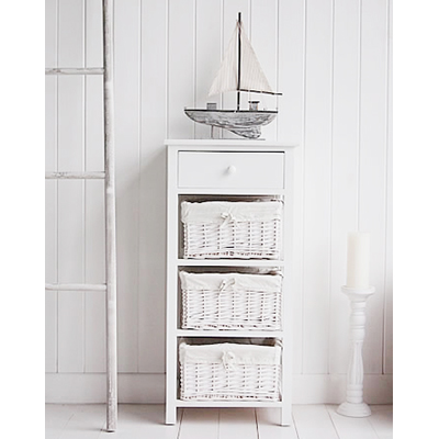 A tall white four drawer bathroom storage unit from The New Haven Range. The bottom drawers are a white lined willow basket, the top drawer has a simple knob pull handle.