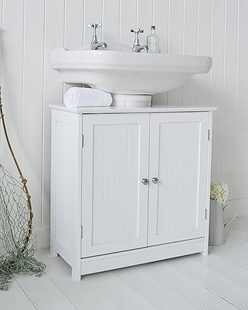 white undersink bathroom storage with knob handle cabinet