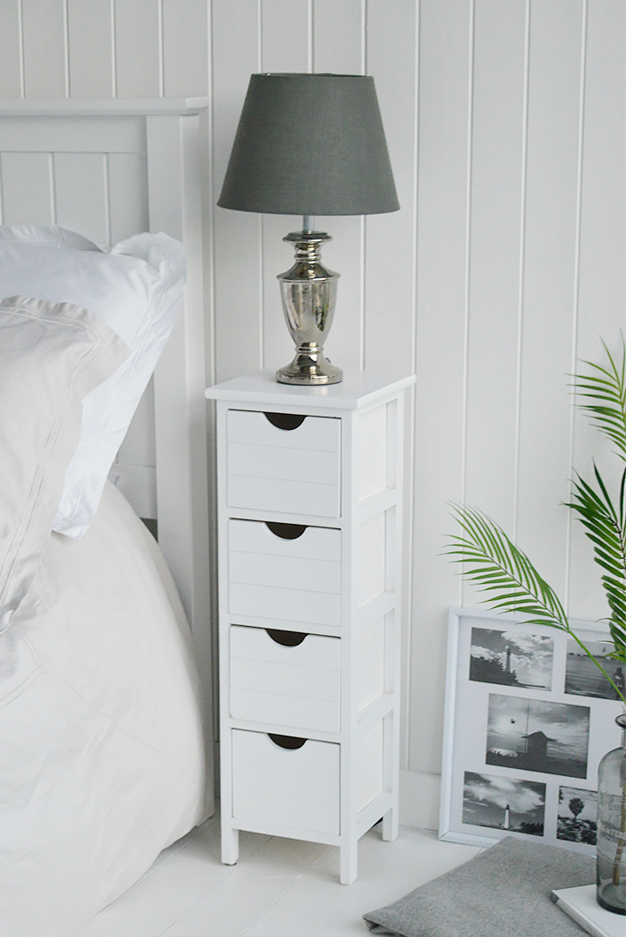 Dorset tall white slim bedside table with 4 drawers at 20cm wide, shown beside a bed and a some greenery