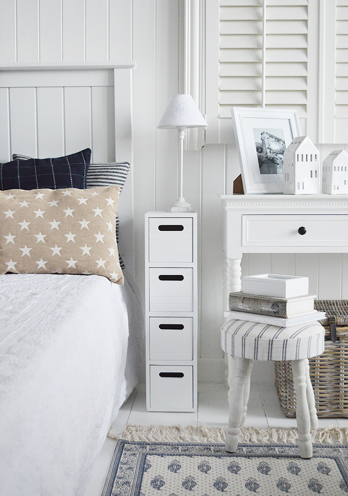 Dorset white very narrow slim white bedside table with 4 drawers for small white bedroom furniture at only 17cm wide. Photograph shows the slim bedside cabinet in between such a small space