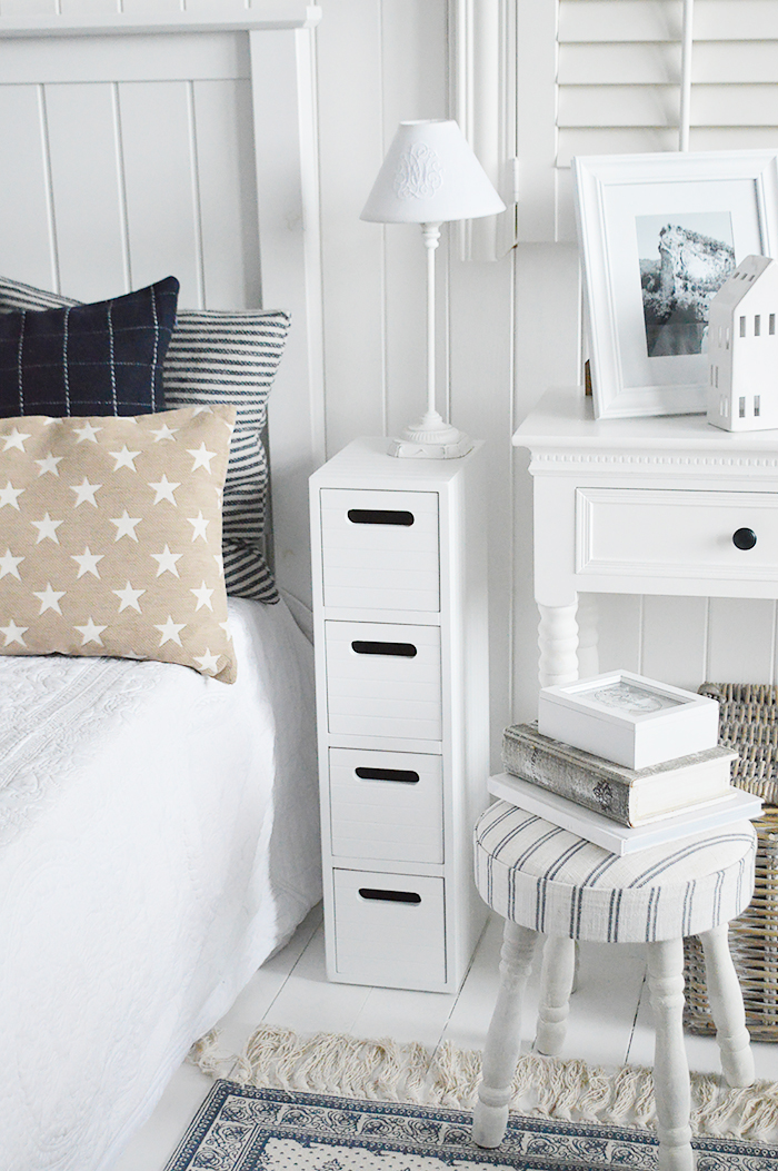 Dorset white very narrow slim white bedside table with 4 drawers for small white bedroom furniture at only 17cm wide. Photograph shows how the cabinet fits into a small space in the bedroom