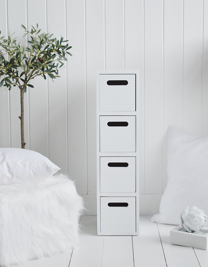 A very narrow white bedside table from the Dorset Range with four drawers