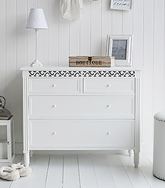 New England simple plain white chest of drawers for a pure white interior. Typical of bedrooms in homes by the sea to create a bright and airy space