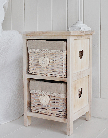 A small bedside table with two lace trimmed lined basket drawers. The hanging heart handles perfectly complement the cut out hearts on the side.