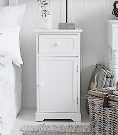 A wooden white painted bedside table with one drawer and a cupboard with simple white knob handles. The drawer and cupboard have a tongue and groove effect design for a classic New England Look.  We love this bedside table with our New England white dressing table, a perfect match for a white bedroom.