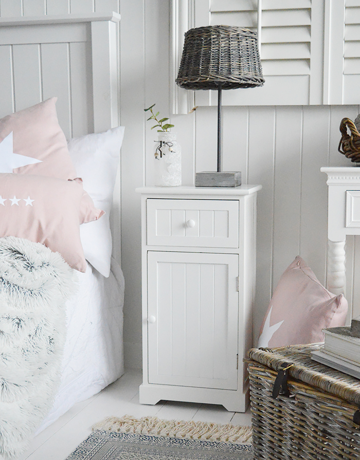 Maine white bedside cabinet with a shelved cupboard and a drawer. An ideal bedside table for any style of New England Coastal or country bedroom. shown here with pink soft furnishings and cushions. Affordable and simple white bedroom furniture for all rooms