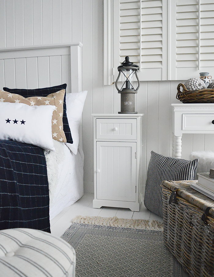 Maine white bedside cabinet with a shelved cupboard and a drawer. An ideal bedside table for any style of New England Coastal or country bedroom. Shown with our Hampshire navy and white check cushions