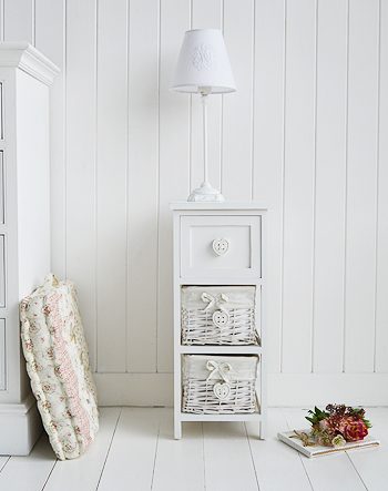 White narrow 25cm bedside table with baskets with sweetheart drawer pulls on the two basket drawers and top wooden drawers, all in a pure white finish