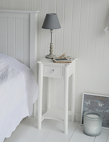 A Narrow Tall White Bedside Table With Drawer And Silver