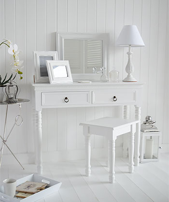 Pure white bedroom interior with a dressing table and stool.
